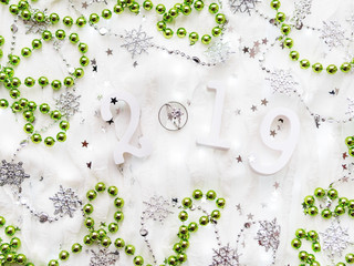 Christmas and New Year background with numbers 2019, green decorations, wedding rings and light bulbs.