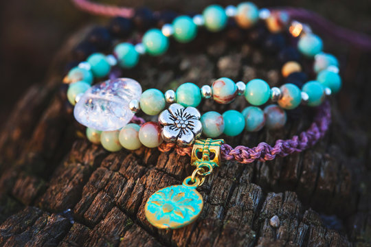 Three bracelets with gemstone beads on wooden background