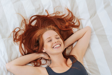 Happy healthy young redhead woman in bed