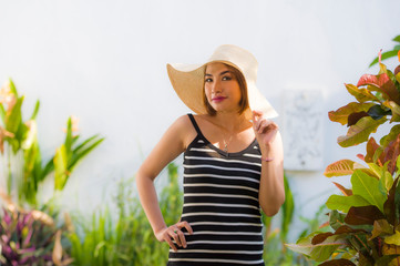 lifestyle portrait of young happy and beautiful woman in Summer hat posing relaxed and smiling cheerful at tropical resort in holidays travel and tourism concept