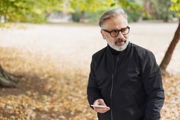 Senior man walking through an autumn park