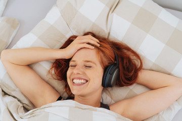 Young woman lying in bed listening to music