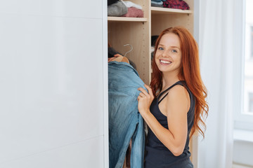 Cheerful woman taking clothes out of wardrobe