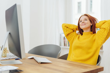 Young dreamy woman sitting in front of computer