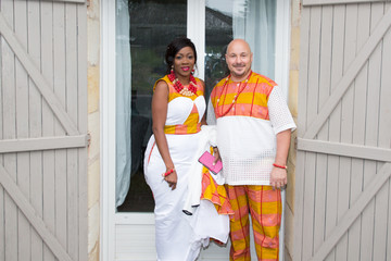 African family in bright ethnic clothes in front of house for wedding mixed race interracial american couple