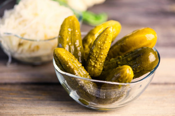 pickled cucumbers  in a glass plate on a wooden board