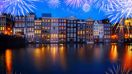 Houses facades over canal with reflections illuminated at night with fireworks, Amsterdam, Netherlands