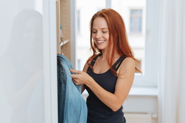 Young woman selecting clothes from her wardrobe