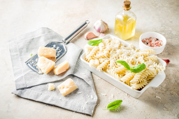 Italian food, fusilli pasta with grated parmesan cheese and basil, light stone table copy space top view