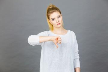 Sad woman showing thumb down gesture