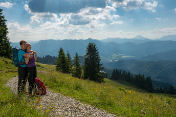 Germany, Bavaria, Brauneck near Lenggries, happy young couple having a break looking at view in alpine landscape