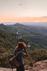 Spain, Barcelona, Montserrat, man with backpack taking photo of view at sunset