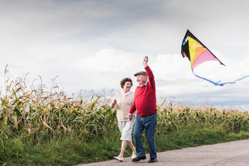 Happy senior couple with kite in rural landscape