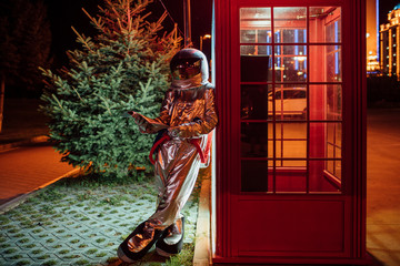 Spaceman leaning against a telephone box at night reading phone book