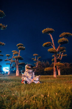 Spaceman in yoga pose siting in a park at night