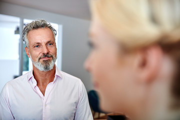 Smiling mature man looking at female colleague in office