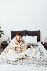 high angle view of sick young man wrapped in blanket sitting on bed at home