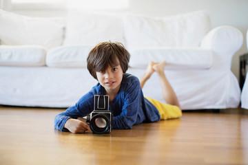 Portrait of boy lying on floor with camera