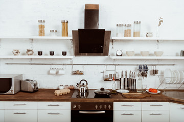 selective focus of modern kitchen interior with frying pan and teapot on stove