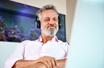 Businessman with headphones using laptop at desk in front of aquarium