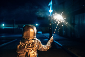 Rear view of spaceman standing outdoors at night holding sparkler