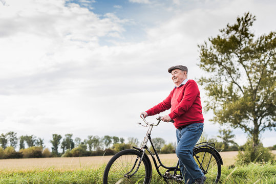 Senior man pushing bicycle in rural landscape