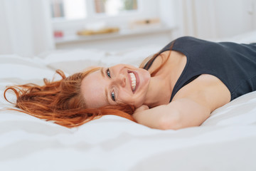Rested happy young woman relaxing in bed