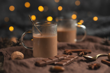 Hot chocolate with cinnamon sticks, anise, nuts and cocoa powder on a rustic wooden background, chocolate and festive garlands