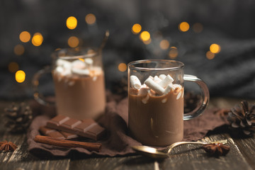 Christmas or New Year's winter hot chocolate with marshmallow in a dark mug, with chocolate, cinnamon and spices with a festive light garland, selective focus, square culture