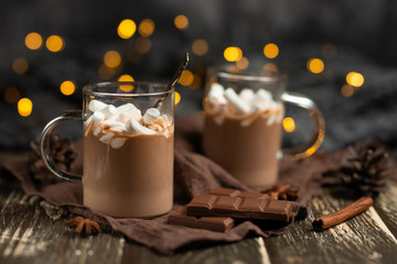 Rich winter hot chocolate with cinnamon sticks and walnuts, chocolate bars in a transparent mug on a wooden board, selective focus, with a festive garland
