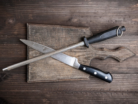 old brown wooden cutting board and knife with sharpening