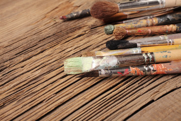 Artistic paintbrushes on the old wooden background