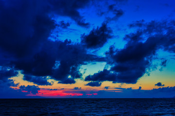 Bright colorful sunset and dark blue rain clouds on the sea with beautiful clouds