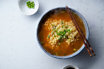 Top view picture of easy japanese ramen with noodles, pork broth, egg and leek in handmade blue ceramic bowl with wooden chopsticks. Concrete background, copy space