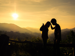 Silhouette of happy young couple in love looking view sunset on the mountain. Pat on the Head