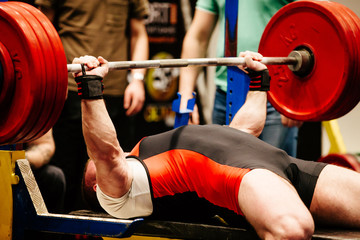 man performs bench press competition powerlifting