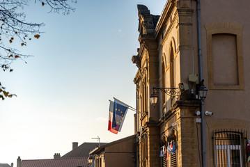 Façade d'un mairie française avec les drapeaux européen et de la France