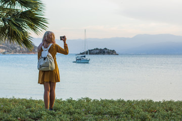 back to camera girl in yellow dress and small white travel bag take photo of tropic south nature landscape view in Mediterranean sea bey with boat and island in shot, evening time, soft colors