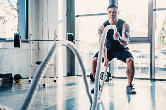 young sportsman working out with battle ropes at gym