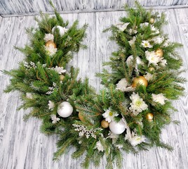 Beautiful Christmas garland with pine needles, white chrysanthemums and Christmas tree decorations with stars and snowflakes on a white wooden background