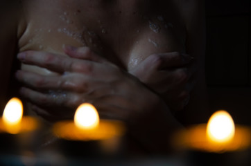 Young beautiful naked woman in the bath by candlelight