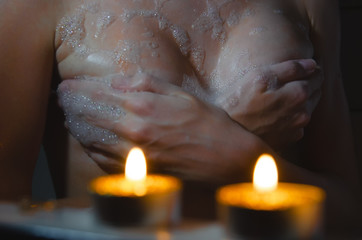 Foto op Canvas Akt naked woman in the bathroom, holding a candle, on the background of his bare chest