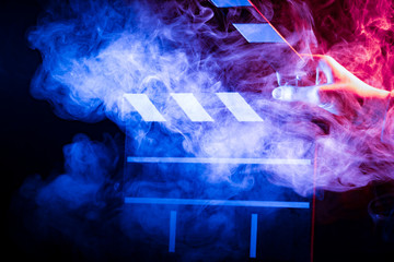 Black and white clapperboard for cinema close up among multicolored red and blue smoke in a man's hand giving a command to start shooting on a black isolated background