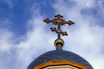 Old Christian church in Kemerovo with golden and gilded domes, brown granite walls against a sky and sunset. Concept of faith in god, orthodoxy, prayer