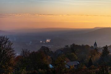 Vue sur un paysage de campagne en Lorraine avec ses collines et son village et son clocher au crépuscule