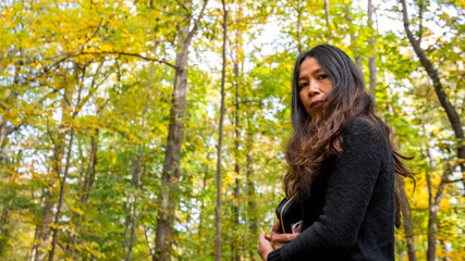Woman in black blouse standing in forest in fall with yellow and green trees