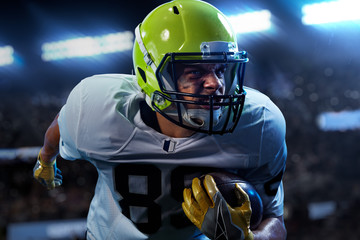 American football sportsman player on stadium in action. Sport wallpaper or advertising