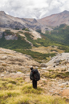 Man with a big backpack on, watching at the immensity, with a long hike ahead, on a beautiful valley on the foreground and cloudy mountains on the background, in Patagonia Argentina, near Bariloche