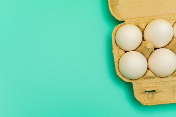 pack of chicken eggs on blue background