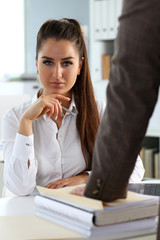 Male worker show pack of papers to busy beautiful female